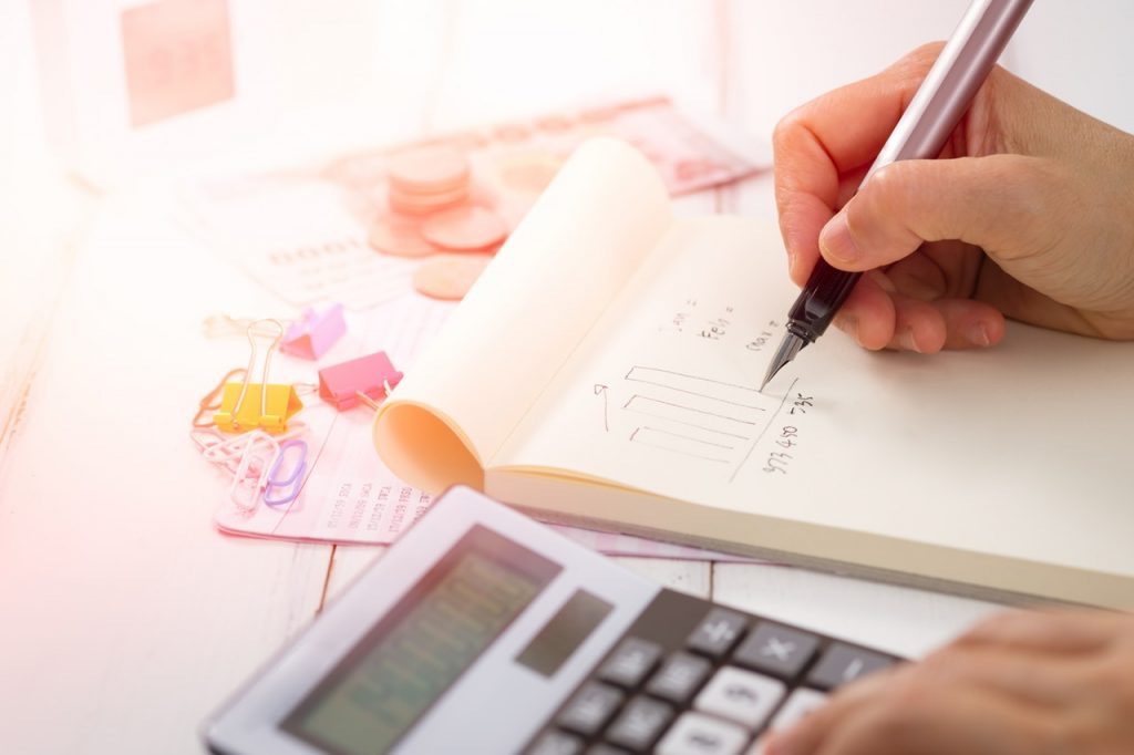 calculadora e outros materiais de papelaria em cima de uma mesa