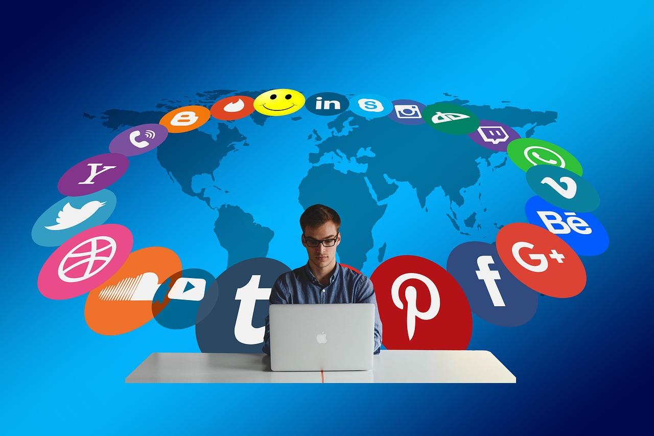 homem usando notebook cercado de mídias sociais