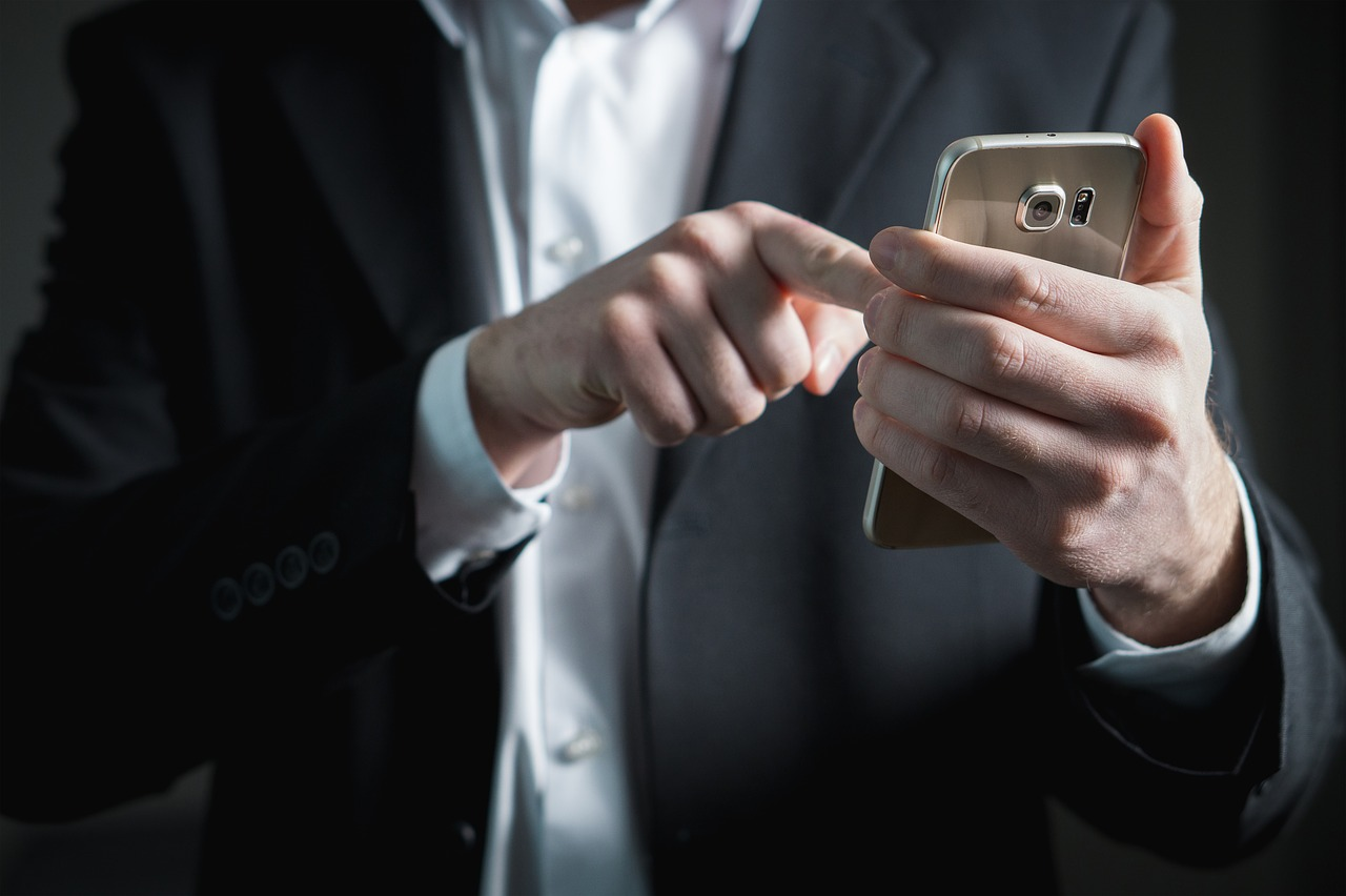 homem clicando no smartphone