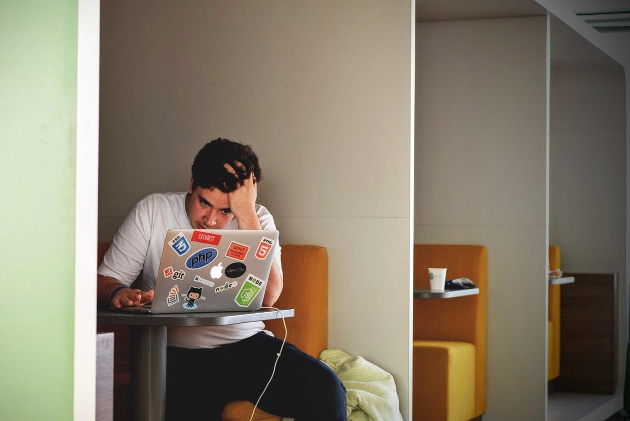 homem com a mao na cabeça usando notebook