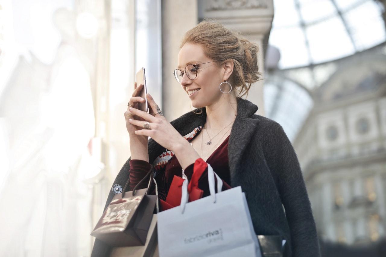 mulher segurando sacolas e smartphone