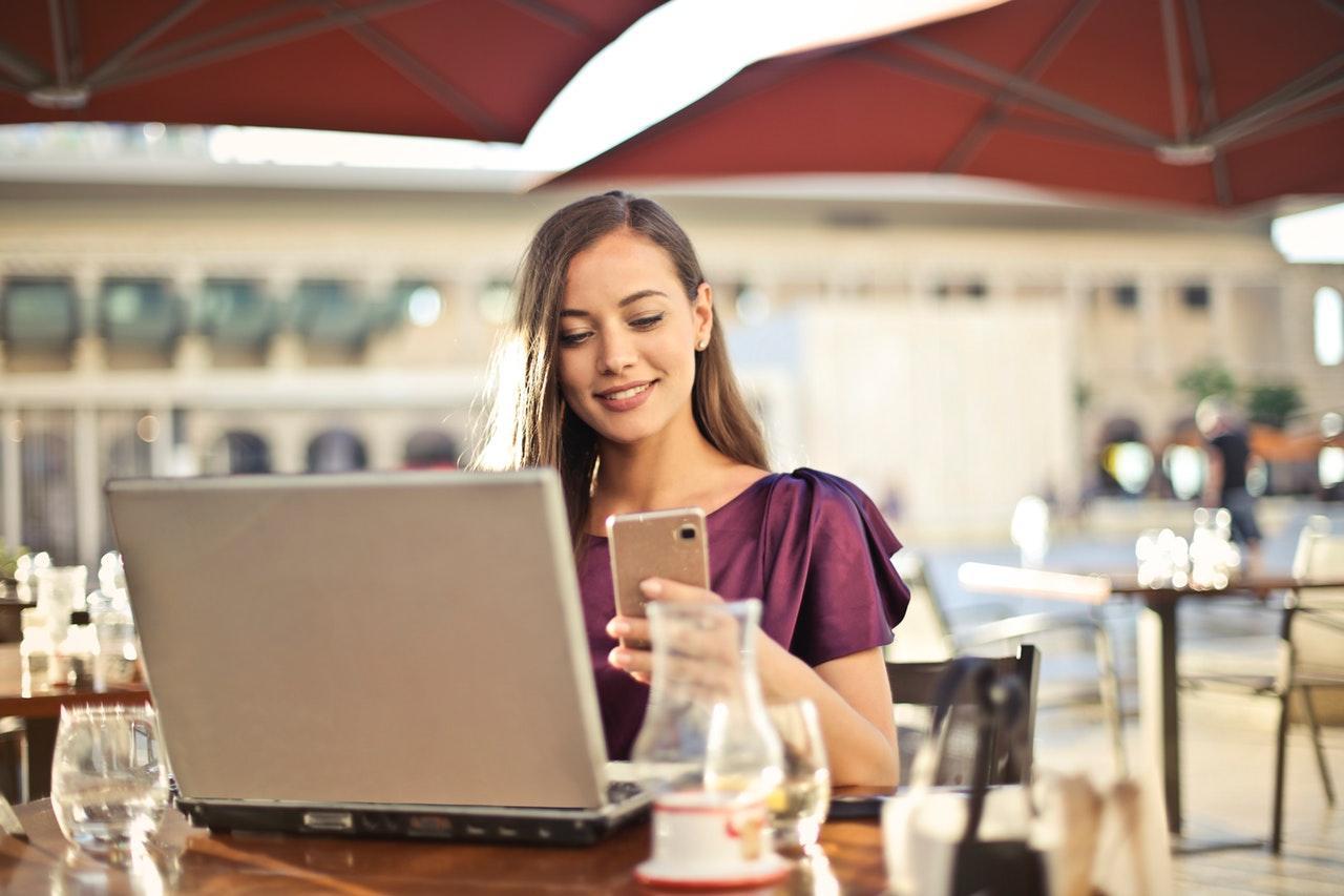 mulher usando smartphone e notebook