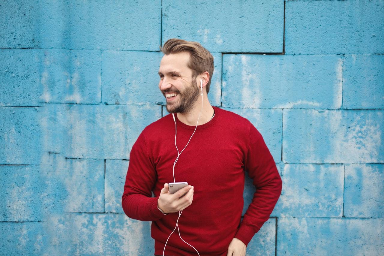 homem usando smartphone com fones de ouvido