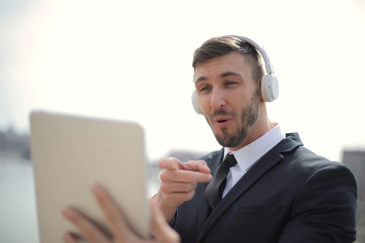 homem usando headphone e segurando tablet