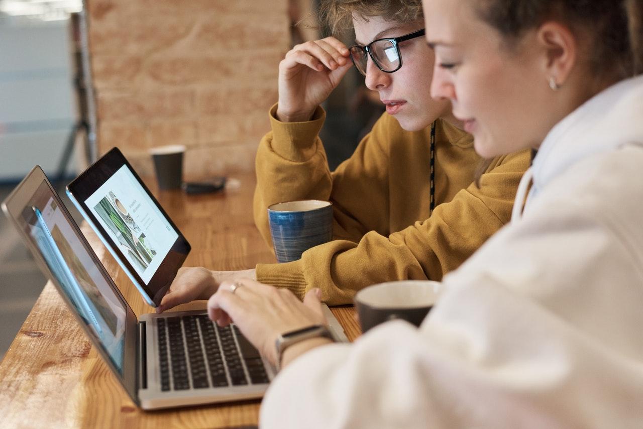 duas mulheres olhando para notebook e tablet