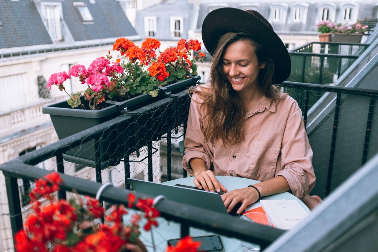 mulher usando laptop na varanda
