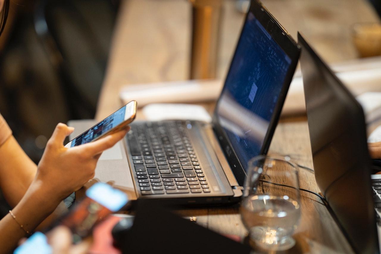 pessoa segurando smartphone e usando notebook